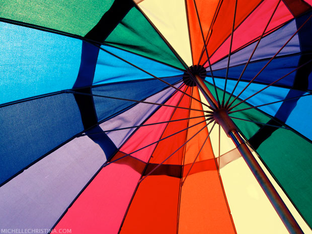 colorful beach umbrella photo by michelle christina